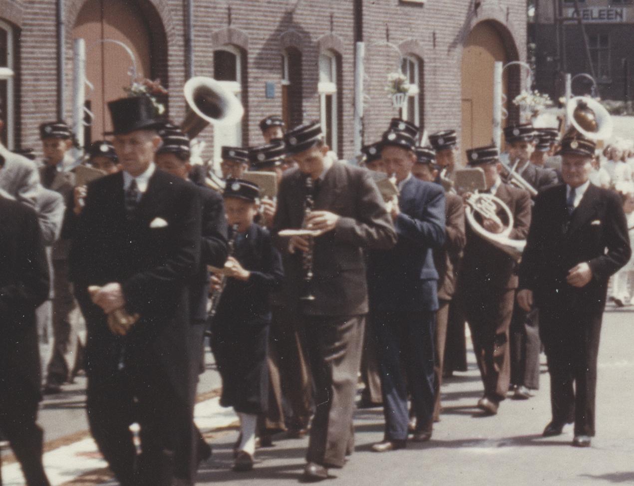 De harmonie tijdens de processie met de uniformpetten